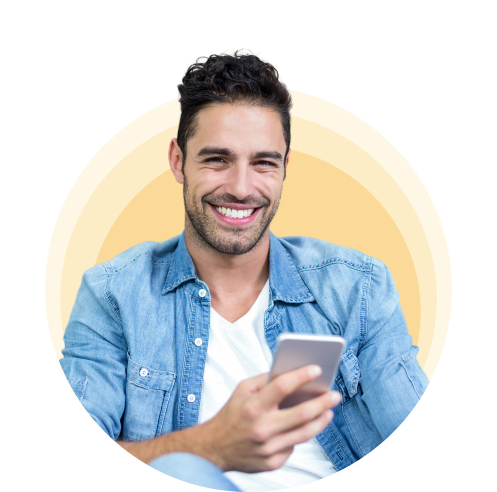 a man with short hair, sitting down and smiling as he uses the OKY app on his smart phone